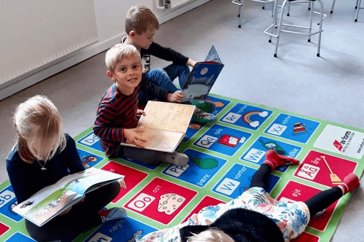 Børn, der sidder på et tæppe med bogstaver på. Børnene læser i bøger.