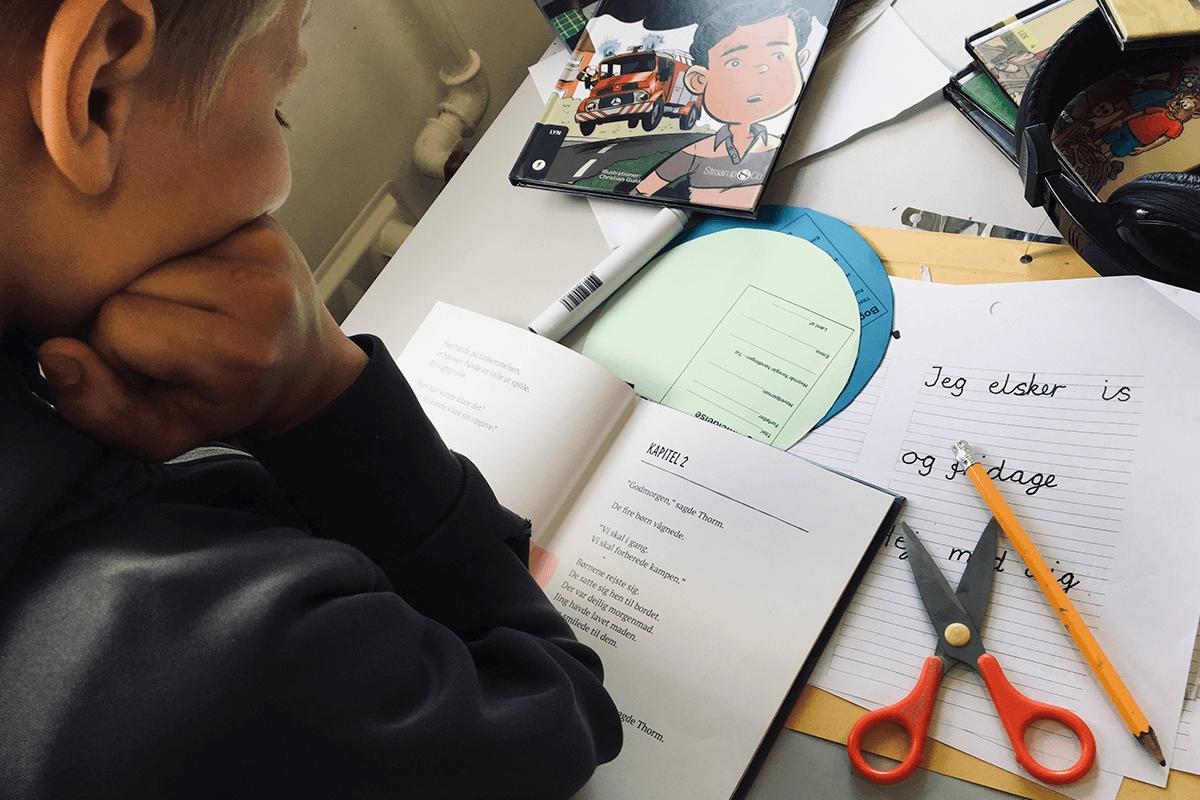 Et barn der sidder og læser ved sit skrivebord
